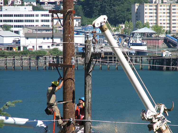 Removing the upper part of the 1980 utility pole along Douglas Highway.